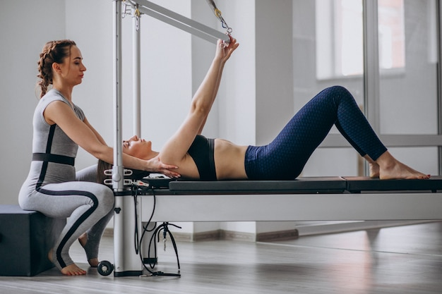Frau mit übendem pilates des pilates kursleiters Kostenlose Fotos