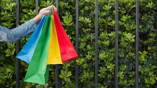 Frau mit vielen hellen einkaufstaschen nähern sich anlagen Kostenlose Fotos