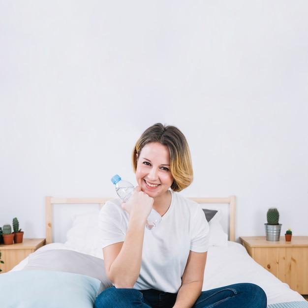 Frau mit wasserflasche auf bett Kostenlose Fotos