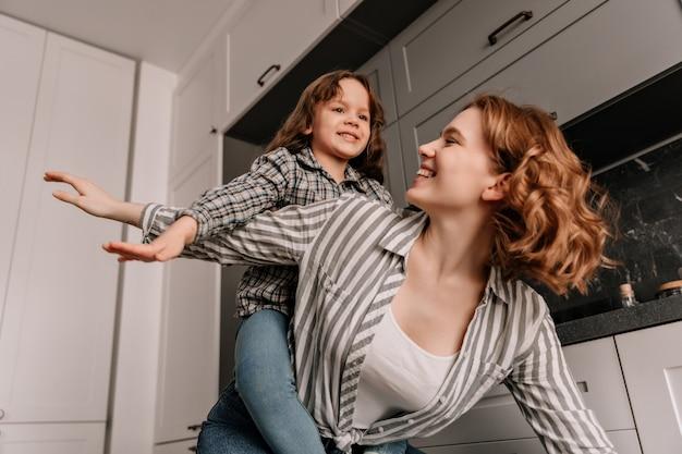 Frau mit welligem haar spielt mit ihrer tochter und posiert wie flugzeuge. Kostenlose Fotos