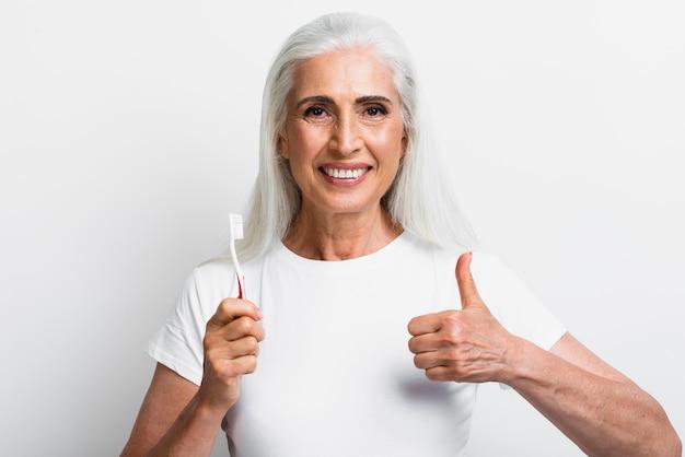 Frau mit zahnbürste mit dem daumen oben Kostenlose Fotos