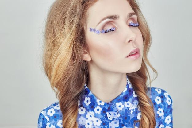 Frau mit zöpfen und blauen blumen auf wimpern Premium Fotos