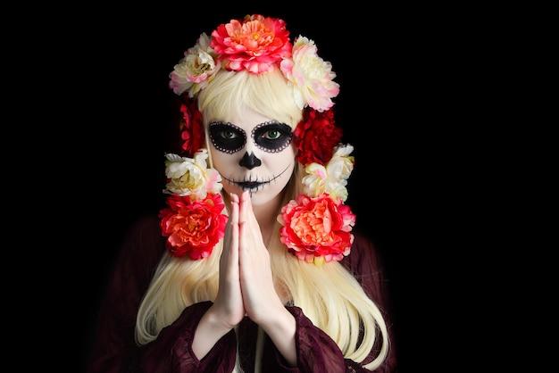 Frau mit zuckerschädel-make-up und blondem haar lokalisiert auf schwarzem hintergrund. tag der toten. halloween. Premium Fotos