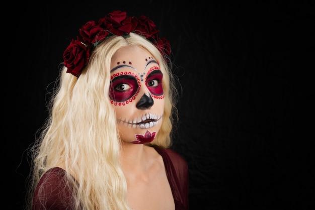 Frau mit zuckerschädel-make-up und blondem haar lokalisiert auf schwarzer wand. Premium Fotos