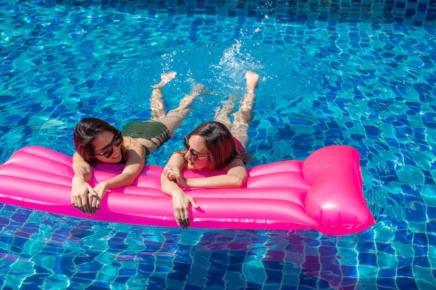 Frau mit zwei asien, die auf rosa aufblasbaren matratzen sich entspannt und liegt. Premium Fotos
