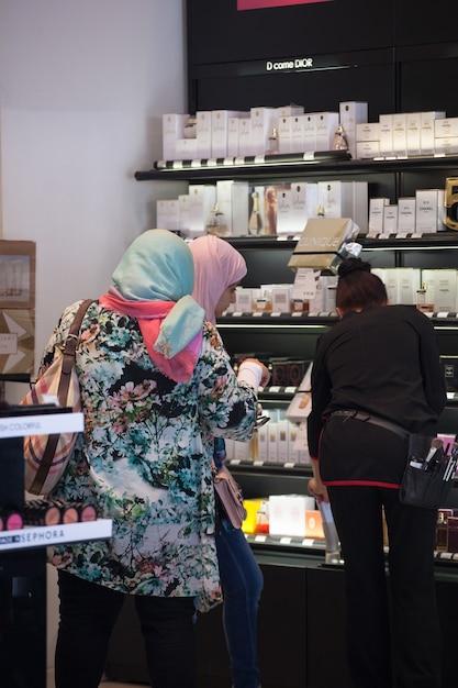 Frau mit zwei moslems im parfüm sho Premium Fotos