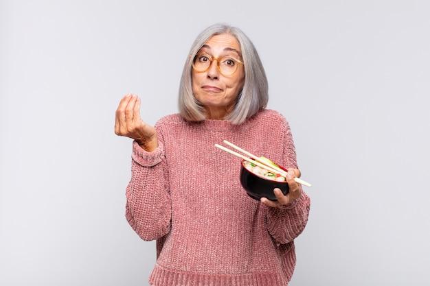 Frau mittleren alters, die capice oder geldgeste macht und ihnen sagt, sie sollen ihre schulden bezahlen! Premium Fotos