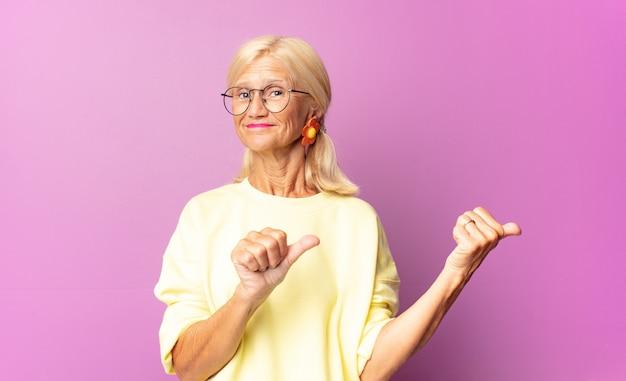 Frau mittleren alters, die fröhlich lächelt und beiläufig zeigt, um platz auf der seite zu kopieren, sich glücklich und zufrieden fühlend Premium Fotos