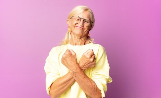 Frau mittleren alters, die fröhlich lächelt und feiert, mit geballten fäusten und verschränkten armen, die sich glücklich und positiv fühlen Premium Fotos
