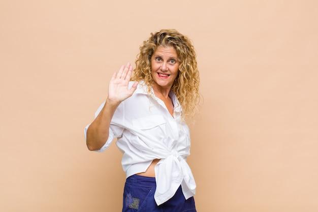 Frau mittleren alters, die glücklich und fröhlich lächelt, hand winkt, sie begrüßt und begrüßt oder sich verabschiedet Premium Fotos