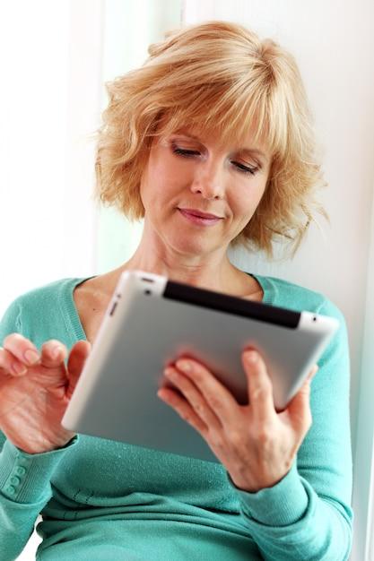 Frau mittleren alters, die mit tablette comper entspannt Kostenlose Fotos