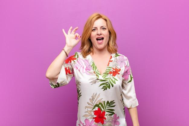 Frau mittleren alters, die sich erfolgreich und zufrieden fühlt, mit weit geöffnetem mund lächelt und mit der hand ein gutes zeichen macht Premium Fotos