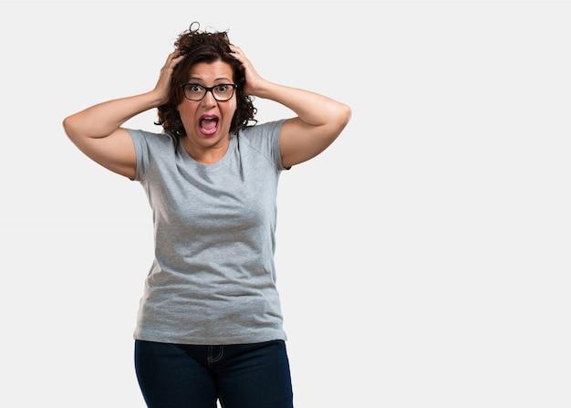 Frau mittleren alters frustriert und verzweifelt, wütend und traurig mit den händen am kopf Premium Fotos