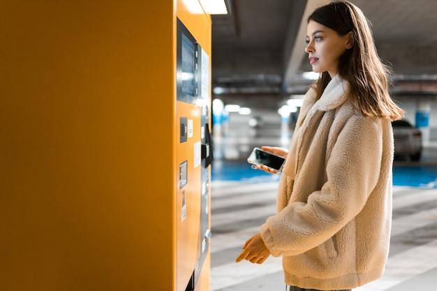 Frau nahe terminal in der tiefgarage Premium Fotos