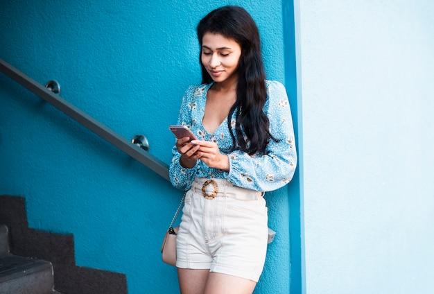 Frau neben der treppe, die das telefon betrachtet Kostenlose Fotos