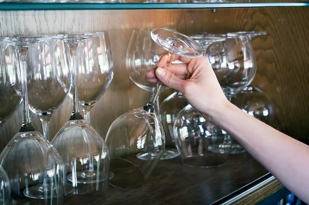 Frau nimmt ein glas aus dem regal Premium Fotos