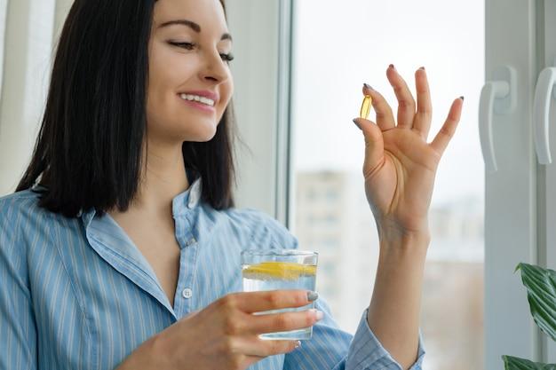 Frau nimmt pille mit omega-3 und hält glas süßwasser mit zitrone Premium Fotos