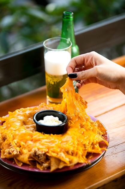 Frau nimmt tortillachips mexikanische chips vom teller, Kostenlose Fotos