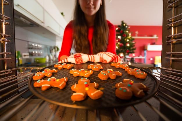 Frau nimmt vorgefertigte lebkuchenmänner aus dem ofen, der für weihnachten sich vorbereitet Premium Fotos