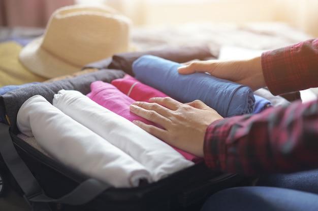 Frau packen kleidung in koffer tasche auf dem bett, bereiten sie sich auf neue reise vor. Premium Fotos
