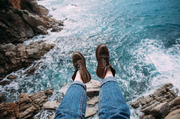 Frau reisende in blauen jeans und klobigen braunen lederstiefeln für wanderabenteuer sitzt am rand der klippe Kostenlose Fotos