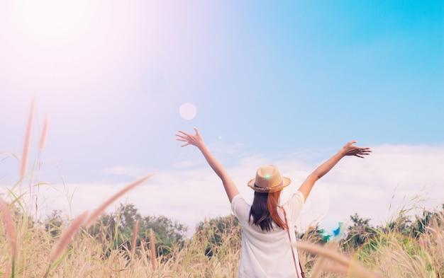 Frau reisender mit kamera holding hut und atmung auf feld von gräsern und wald, wanderlust reise-konzept, platz für text, atmosperic epischen moment Kostenlose Fotos