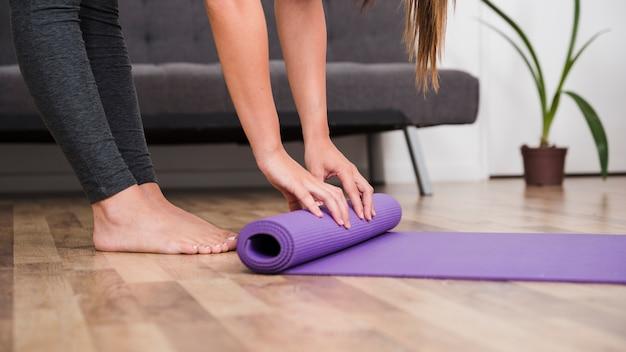 Frau rollende yogamatte Kostenlose Fotos