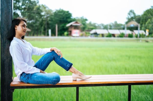 Frau saß auf einem holzbalkon und legte die hände auf die knie Kostenlose Fotos