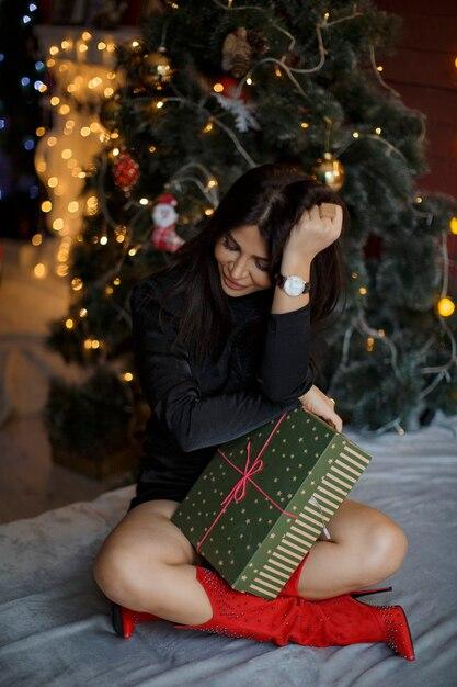 Frau schaut auf das bett und hält ihr geschenk Premium Fotos