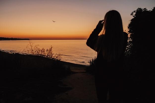 Frau schaut auf den abendsee Kostenlose Fotos