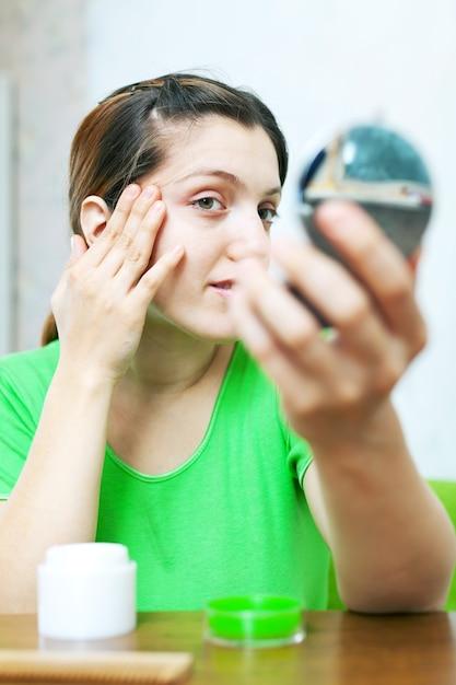 Frau schaut auf ihre haut Kostenlose Fotos