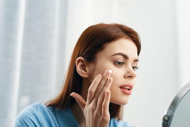 Frau schaut sich im spiegel an und schmiert sahne Premium Fotos