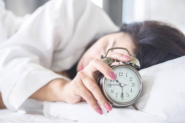 Frau schläft auf dem bett hand wecker ausschalten Premium Fotos