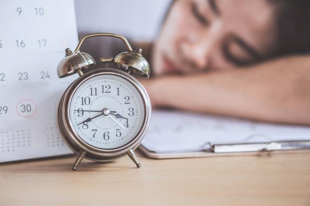 Frau schläft bei der arbeit mit stichtag kalender und uhr Premium Fotos