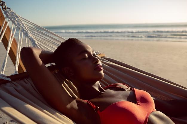 Frau schläft in einer hängematte am strand Kostenlose Fotos