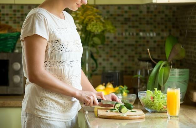 Frau schneidet gurken für einen salat auf der küche Kostenlose Fotos