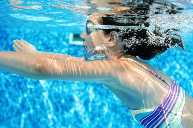 Frau schwimmt unter wasser im schwimmbad, glücklich aktive teenager mädchen taucht und hat spaß unter wasser, kind fitness und sport im familienurlaub im resort Premium Fotos