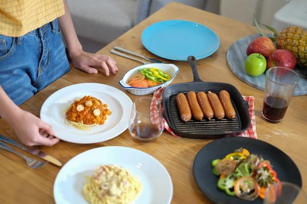 Frau servieren und bereiten das essen für eine mahlzeit oder party Premium Fotos