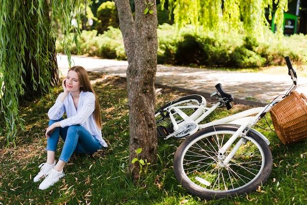 Frau sittin auf gras nahe bei fahrrad Kostenlose Fotos