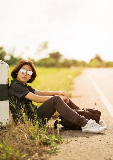 Frau sitzen mit dem rucksack, der entlang einer straße in der landschaft per anhalter fährt Premium Fotos