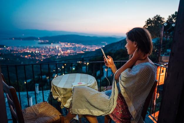 Frau sitzt auf dem balkon, im hintergrund die nachtstadt Kostenlose Fotos