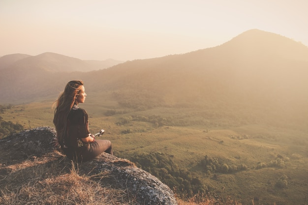 Frau sitzt auf dem boden suchen bei sonnenuntergang Kostenlose Fotos