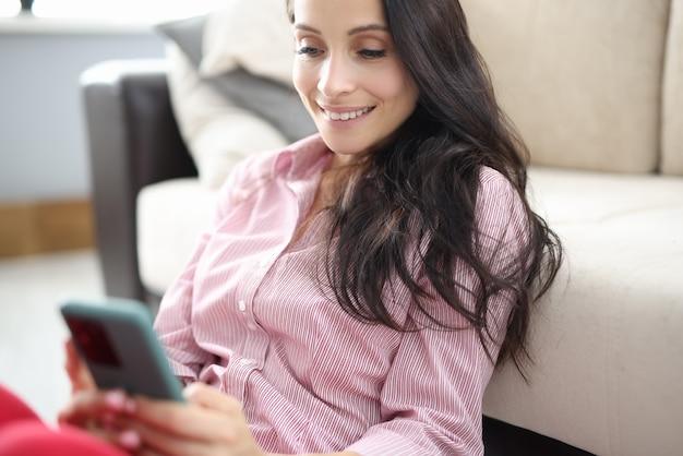 Frau sitzt auf dem boden um dokumente mit diagrammen mit kommerziellen indikatoren, die tablette in ihren händen halten. Premium Fotos