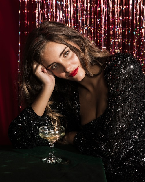 Frau sitzt auf einem tisch mit einem glas champagner Kostenlose Fotos
