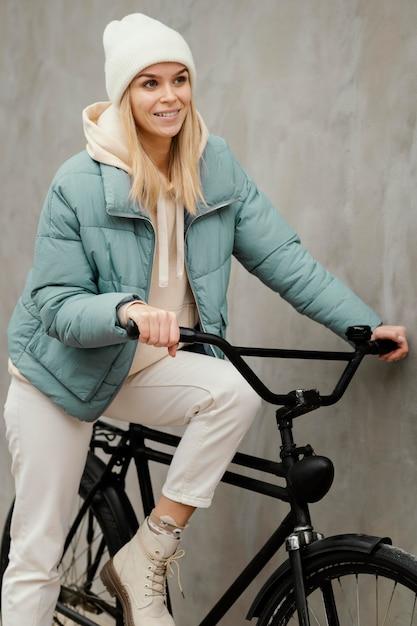 Frau sitzt auf ihrem fahrrad und lächelt Kostenlose Fotos