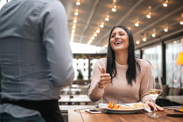 Frau sitzt im restaurant und zeigt daumen zum kellner. Premium Fotos
