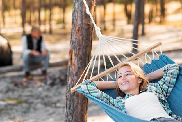 Frau sitzt in der hängematte verwischte mann im hintergrund Kostenlose Fotos