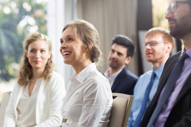 Frau sitzt in der öffentlichkeit lächelnd Kostenlose Fotos