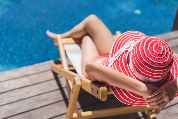 Frau sitzt in einem stuhl, der im sommer sich entspannt Premium Fotos