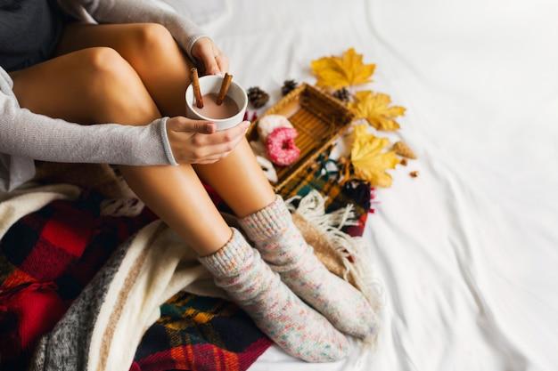 Frau sitzt in ihrem bett mit büchern und trinkt kaffee mit zimt, keksen und glasierten donuts. Kostenlose Fotos